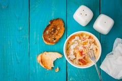 Critique despiadadamente el cocotte con la tostada, la sal, la pimienta y la bifurcación en la opinión de sobremesa de madera ciá Imagenes de archivo