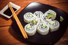 Critique despiadadamente el rollo de sushi con el aguacate en la placa negra foto de archivo libre de regalías