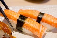 Critique despiadadamente el sushi del palillo, sushi de Kanikama con los palillos imagen de archivo libre de regalías
