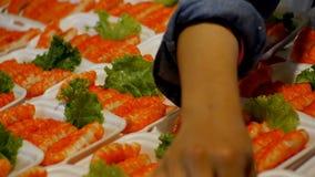 Critique despiadadamente los palillos o las chuletas de los pescados en una placa en el contador Comida asiática de la calle en T almacen de video