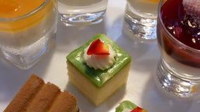 Critique el tiro de la crema batida del mango y de la mini torta en la tabla dentro del restaurante almacen de video