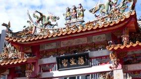 Critique el tiro de la decoración colorida tradicional en el templo chino al lado del edificio en día soleado almacen de video