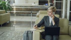 Critique el tiro de la empresaria ocupada rubia que se sienta en butaca en el pasillo del hotel que habla el teléfono móvil, escr metrajes