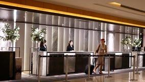 Critique el tiro de la incorporación del asistente de vuelo para el sitio en el hotel en el contador de la recepción almacen de video