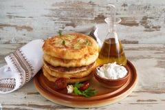 Critique las tortillas fritas de la patata servidas con la salsa del yogur y las verduras frescas imagenes de archivo