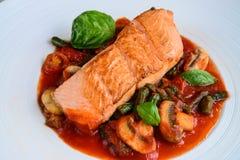 Critique los salmones chamuscados con las setas en caldo del tomate de la albahaca foto de archivo libre de regalías