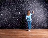 Écriture d'étudiant sur le grand tableau noir avec des symboles mathématiques Image stock