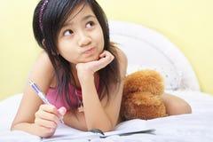Écriture de petite fille son agenda Photographie stock libre de droits