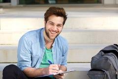 Écriture heureuse d'étudiant universitaire sur le bloc-notes dehors Photographie stock