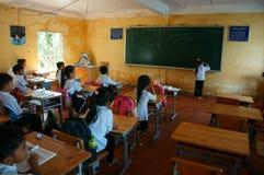 Écriture primaire d'élève sur le tableau noir dans le temps d'école Images libres de droits