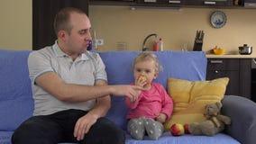 Córka daje kąskowi jabłko dla ojca i mokietu niedźwiedzia zabawki Ojczulek całuje dziecka zbiory wideo
