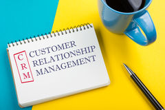 CRM customer relation management Text written on notebook page, pen and coffee cup. Royalty Free Stock Photos