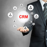CRM (Customer Relationship Management) sign shown by a businessman. CRM (Customer Relationship Management) sign with people icons linked as network on Stock Image