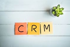 CRM word with paper note on white wood table background Royalty Free Stock Photography