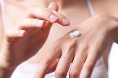 Crème sur la main de femmes Photographie stock libre de droits