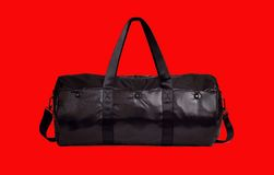 Crna sportska putna torba. Black sports suitcase isolated on red background Stock Photography