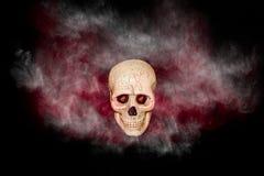 Crâne avec de la fumée rouge et noire sur le fond noir Photographie stock libre de droits