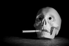 Crâne humain avec la cigarette Photo stock