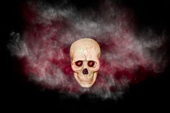 Cráneo con humo rojo y negro en fondo negro Fotografía de archivo libre de regalías