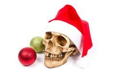 Cráneo divertido en el sombrero Santa Claus en el fondo blanco Fotografía de archivo libre de regalías