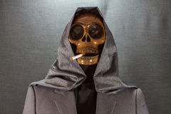 Cráneo humano que fuma un cigarrillo en un fondo negro, cigarrillo muy peligroso para la gente No fume por favor Día de Halloween Foto de archivo libre de regalías