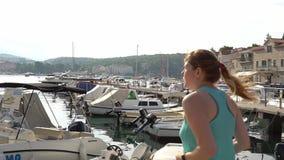 Croácia Makarska setembro de 2018 Uma moça corre ao longo do cais ao longo da costa de mar vídeos de arquivo