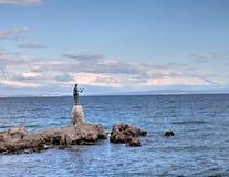 Croacia: Escultura de bronce/estatua de la doncella con la gaviota en fondo un mar en Opatija Foto de archivo libre de regalías
