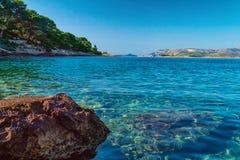 Croacia pintoresco ofrece a turistas las playas prístinas del Adriático, rodeadas por los árboles de pino y las rocas Fotografía de archivo libre de regalías
