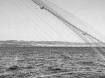 Croata Adriático en la costa de Rijeka con la red de pesca en el primero plano en monocromo Imagen de archivo