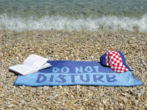 Adriatic sea. Wet towel do not disturb with open book and  Croatia cap on a pebbles beach an water splash waves in shallow at crystal clear Adriatic sea Stock Photos