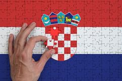 Croatia flag is depicted on a puzzle, which the man`s hand completes to fold.  royalty free illustration