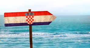 Free Croatia Flag On Wooden Table Sign On Beach Background. There Is Beach And Clear Water Of Sea And Blue Sky Stock Image - 149013891