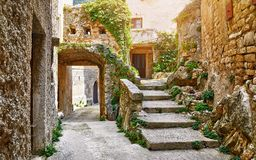 Croatia Istria. Ancient abandoned medieval town Plomin. Old stone street with ruined walls houses and stairs overgrown by ivy plants stock images