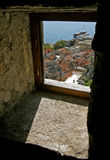 Croatia -Omis view through the window. View of old pirate town Omis and the port city through the window of the old fort Mirabela. Vertical color photo Royalty Free Stock Images