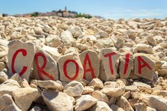 Croatia painted on stones beach with dalmatian town in the background Royalty Free Stock Images