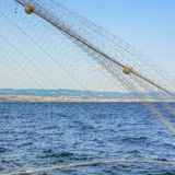 Croatian Adriatic at the coast of Rijeka with fishing net in the foreground.  Stock Images