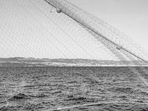 Croatian Adriatic at the coast of Rijeka with fishing net in the foreground in monochrome.  Stock Image