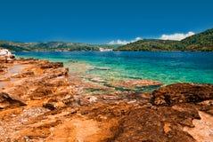 Croatian Adriatic coastline. Vivid turquoise blue sea, golden stones and green islands Royalty Free Stock Photo