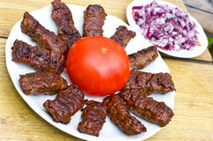 Croatian cevapcici with red onion and tomato Royalty Free Stock Photos