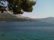 Croatian coastline. Mountains, blue waters, and islands outline Croatia's beautiful Mediterranean Sea coast - strolling along the rock Royalty Free Stock Photo