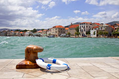 Croatian costal town, windy sea, bollard and life buoy Royalty Free Stock Image