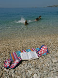 Croatian English Dictionary. People in sea and Croatian English Dictionary on stone beach stock images