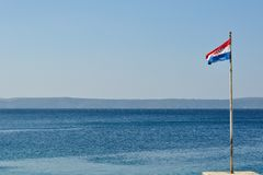 Croatian flag flying at windy day with adriatic sea in background Stock Images
