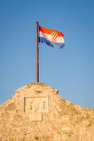 Croatian flag on the fortress wall above the ancient entrance Stock Photos