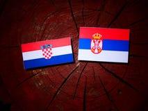 Croatian flag with Serbian flag on a tree stump isolated. Croatian flag with Serbian flag on a tree stump stock photos