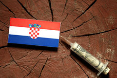 Croatian flag on a stump with syringe injecting money Royalty Free Stock Photography