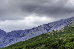 Croatian forest with clouds in mountains - Brela, Makarska Riviera, Croatia. Croatian forest with clouds in mountains near Brela, Makarska Riviera, Croatia royalty free stock photo
