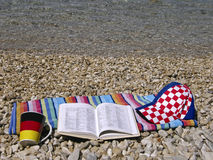 Croatian German dictionary. Open croatian German dictionary on stone - pebbles beach and shallow of a crystal clear Adriatic sea. Horizontal color photo Royalty Free Stock Image