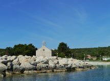 The Croatian island Premuda. The Krijal church with the graveyard situated at the harbor of the little island Premuda in the northern Adriatic sea of Croatia royalty free stock images
