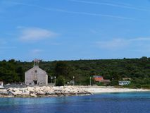 The Croatian island Premuda in the Mediterranean. The Krijal church with a grafeyard situated at the local harbour on the small island Premuda in the Adriatic royalty free stock images